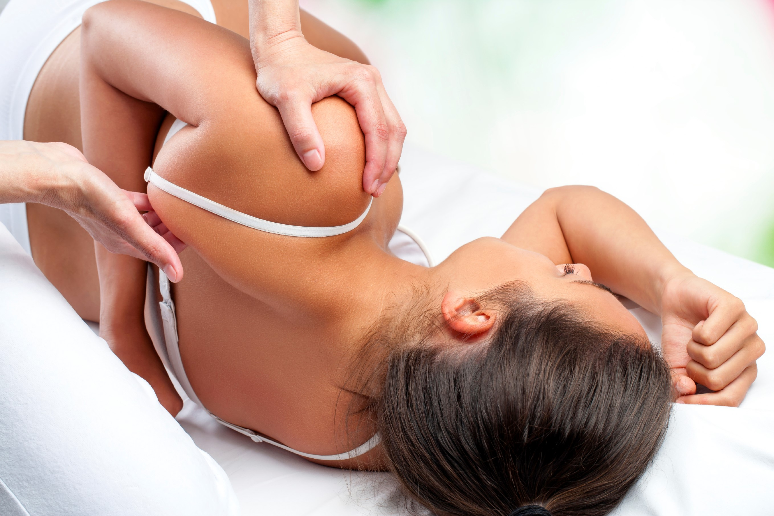 Close up top view of osteopath doing healing treatment on female shoulder blade.
