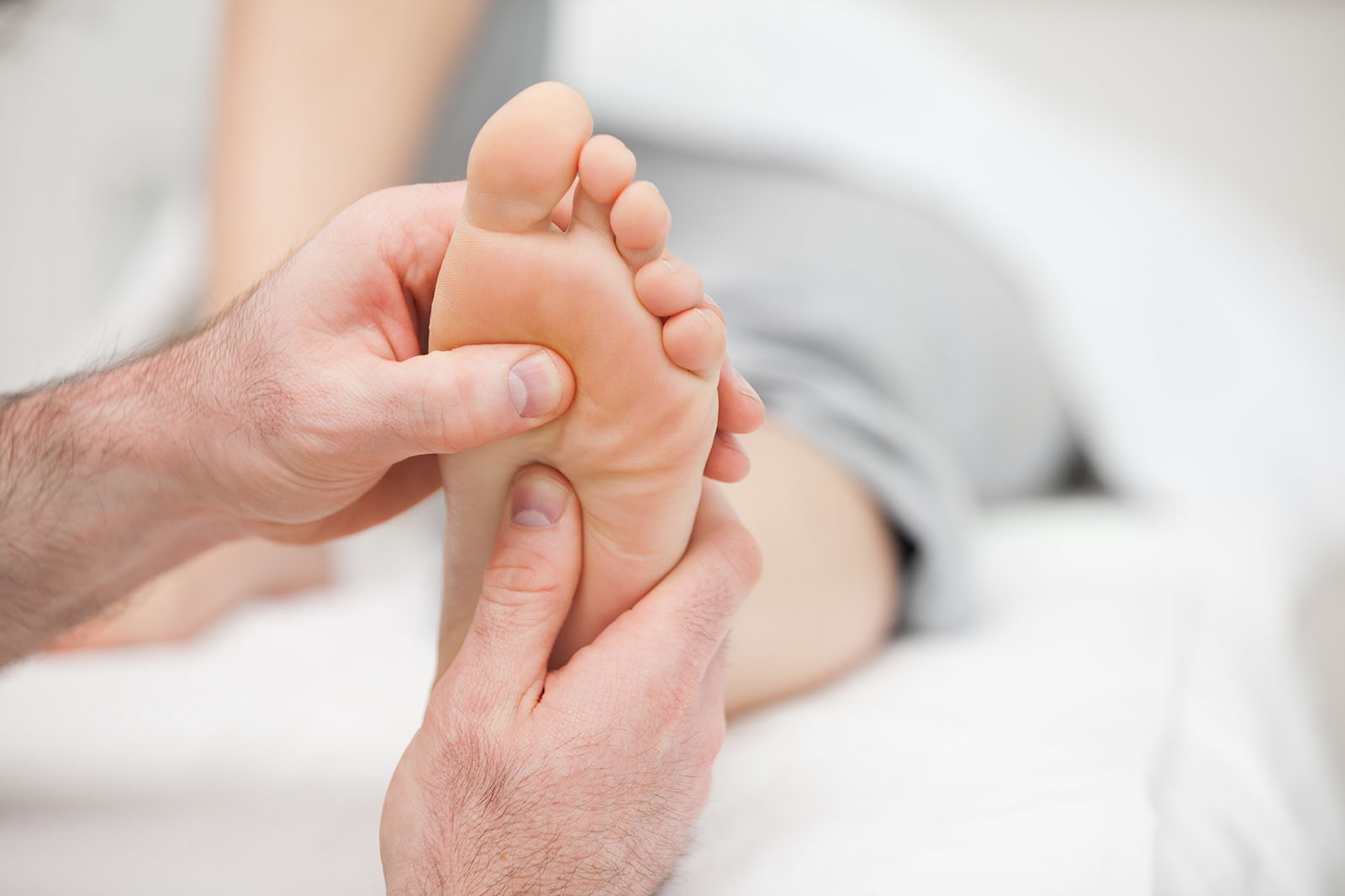 Patient receiving a foot massage in a room